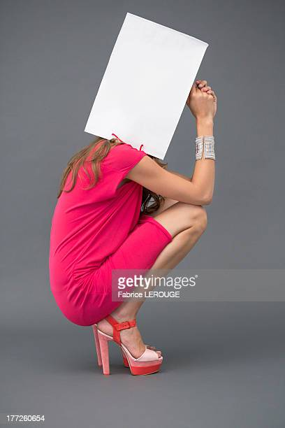 Woman holding a shopping bag over her face