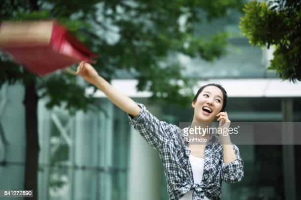 woman holding a shopping bag while receiving a call