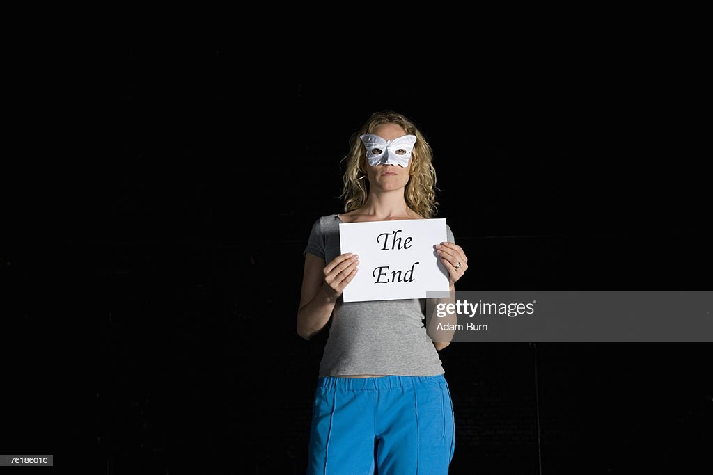 A woman holding a sign for 'The End' : Stock Photo
