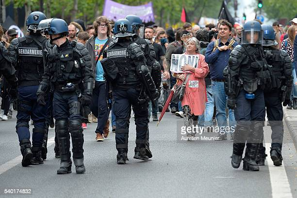 A woman holding a sign walks toward riot police during an antilabour refom law demonstration on June 14 2016 in Paris France According to the police...