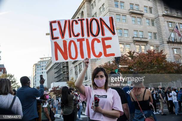 Woman holding a sign with EVICTION NOTICE written on it, stands at Black Lives Matter Plaza near the White House while celebrating the election win...