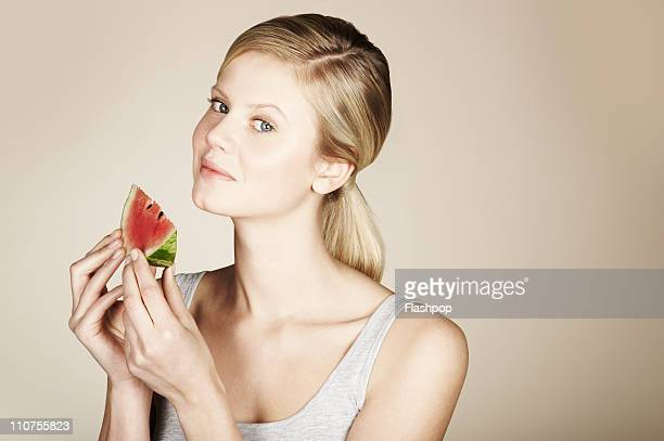 Woman holding a slice of fresh water melon