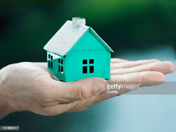 A woman holding a small house on her palm, focus on the hand