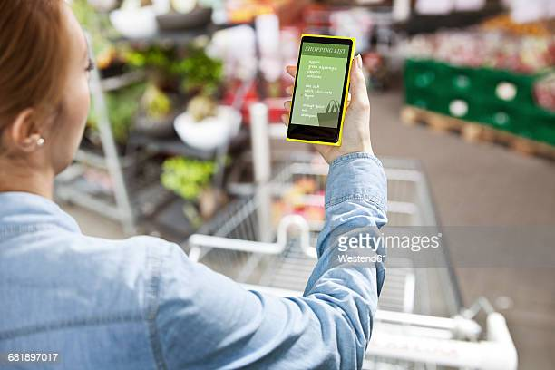 Woman holding a smart phone with a shopping list in front of a super market