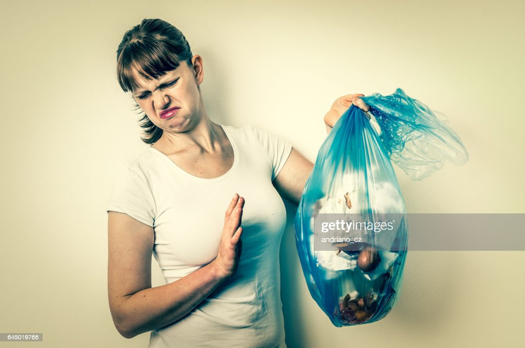Woman holding a smelly garbage bag : Stock Photo