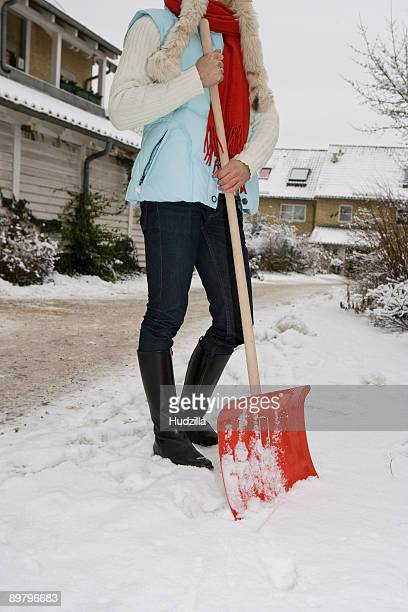 A woman holding a snow shovel, outdoors