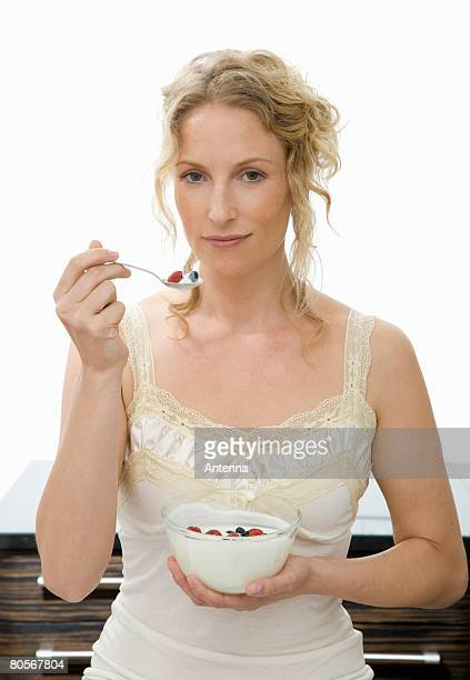 A woman holding a spoon of yogurt and raspberries up to her mouth