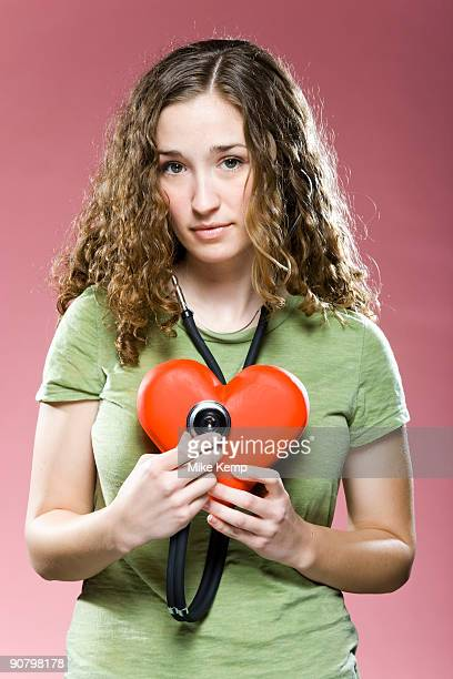 woman holding a stethoscope up to her heart
