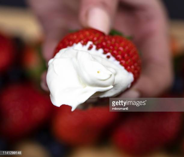 woman holding a strawberry with whipped cream - cream stock pictures, royalty-free photos & images