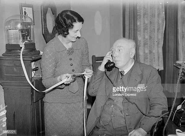 A woman holding a strip of information from a ticker tape machine while her companion speaks on the telephone