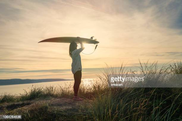 woman holding a surfboard above her head at sunset, sand dunes at gwithian towan beach, cornwall. - surf stock pictures, royalty-free photos & images