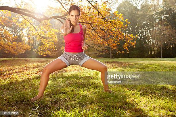 Woman holding a tai chi pose in autumnal park