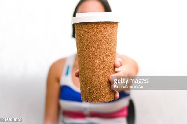a woman holding a takeout coffee - cork material stock pictures, royalty-free photos & images