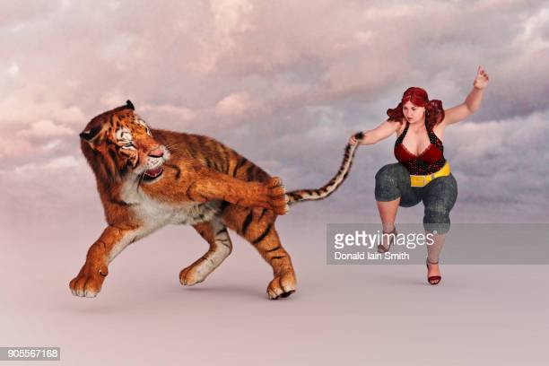 woman holding a tiger by the tail - fat cat stock photos and pictures