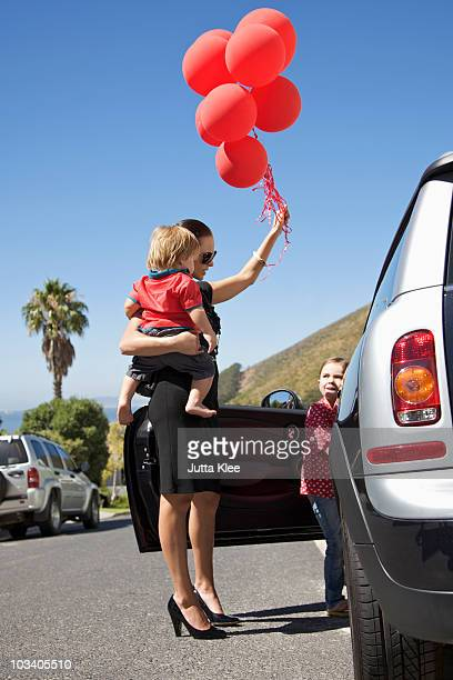A woman holding a toddler and a bunch of balloons next to a girl getting into a car