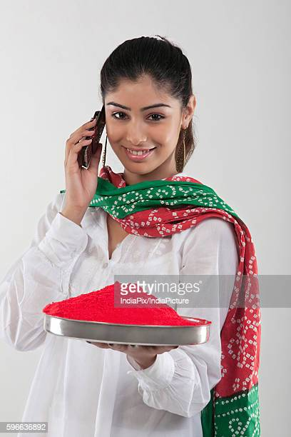 woman holding a tray of colours while talking on the mobile phone - hinduism stock pictures, royalty-free photos & images
