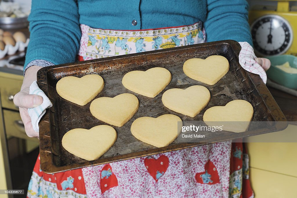 Woman holding a tray of heart shaped cookies : Stock Photo