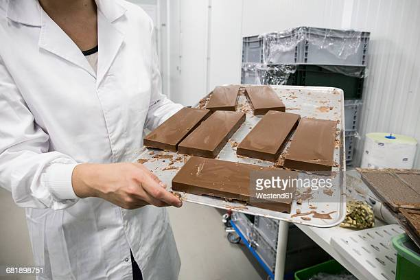 woman holding a tray with chocolate nougat in a chocolate factory - chocolate factory bildbanksfoton och bilder