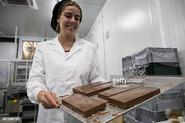 Woman holding a tray with chocolate nougat in a chocolate factory