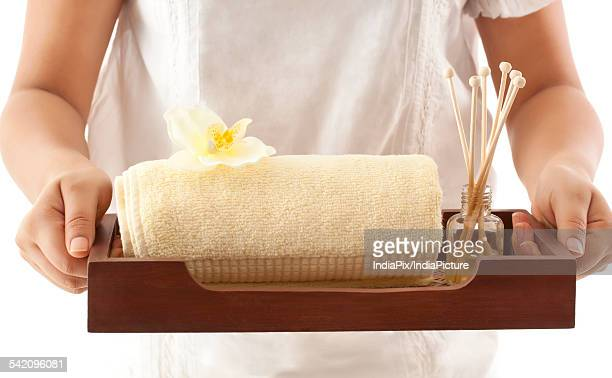 Woman holding a tray with towel and reed diffuser