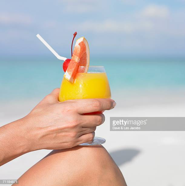 Woman holding a tropical drink at the beach