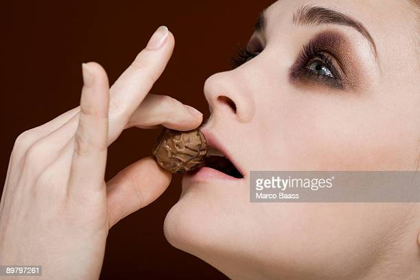 A woman holding a truffle to her lips