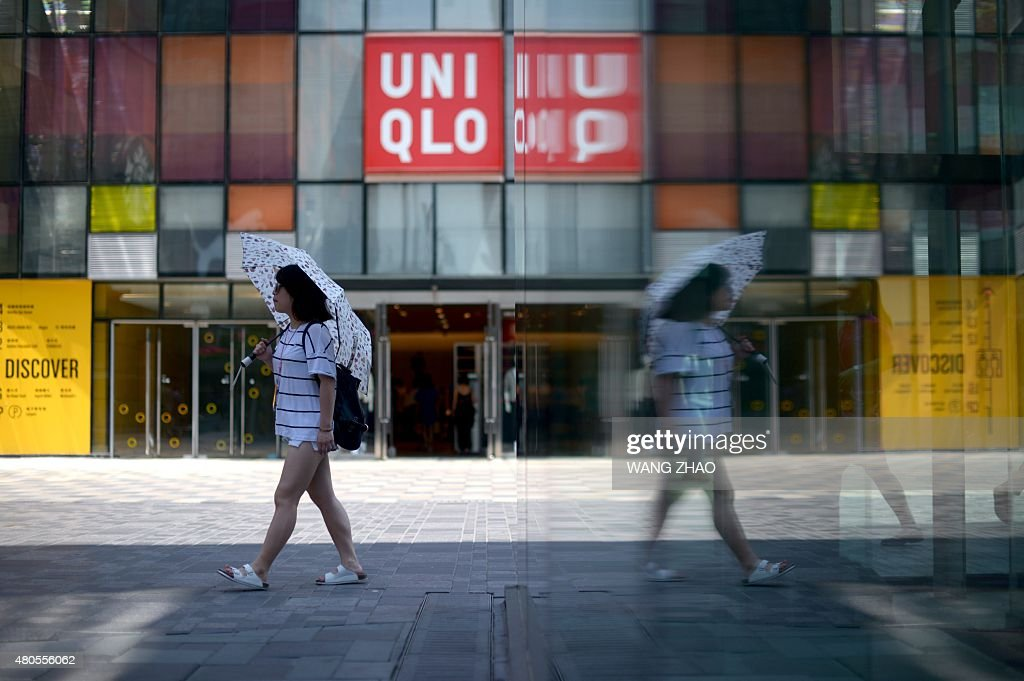 A woman holding a umbrella walks past a shopping mall in Beijing on July 13, 2015. China's total trade slumped in the first half of this year, official data showed on July 13, falling well short of the government's targets and dealing a blow to the global economy from its biggest trader in goods.