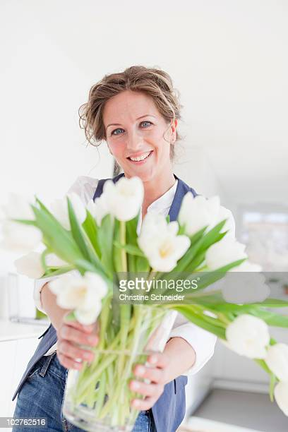 Woman holding a vase with white tulips