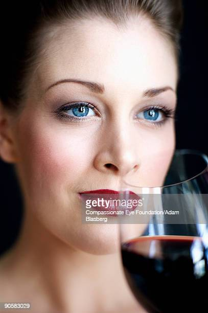 woman holding a wine glass close to her mouth