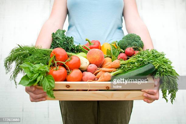 A woman holding a wooden crate filled with vegetables