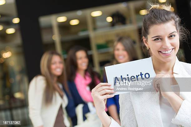 Woman holding 'abierto' sign in mall