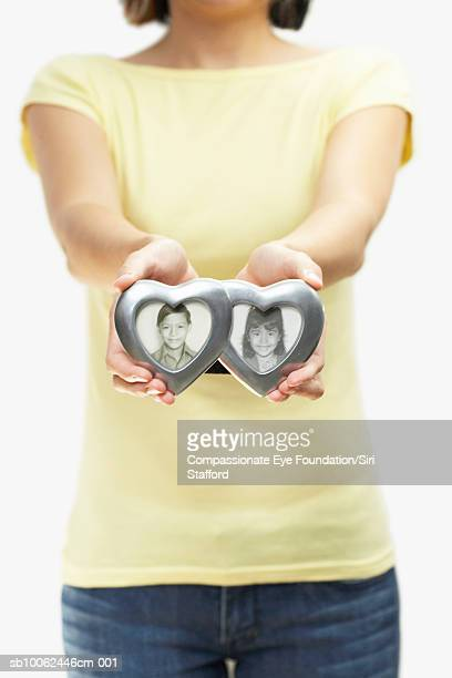 """woman holding aged, black and white framed photographs of children, close-up of hands (mid section) - """"compassionate eye"""" fotografías e imágenes de stock"""