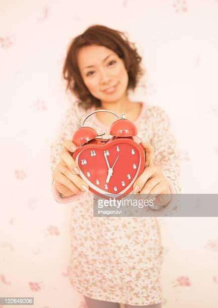 A woman holding alarm clock