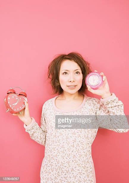 A woman holding alarm clocks