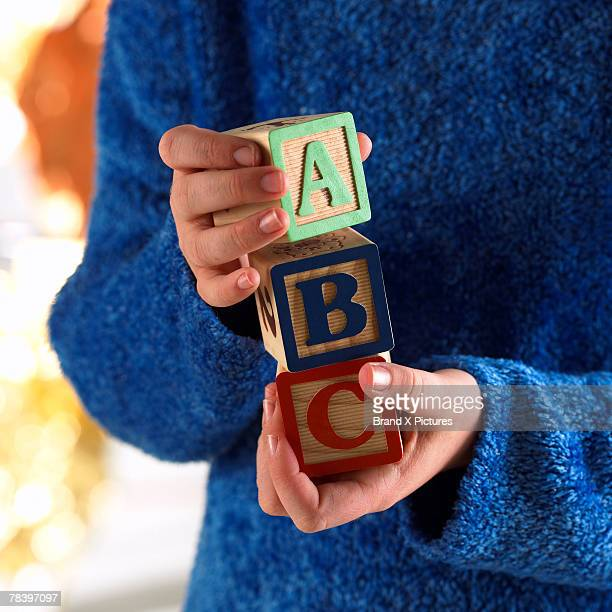 woman holding alphabet blocks - abc stock pictures, royalty-free photos & images