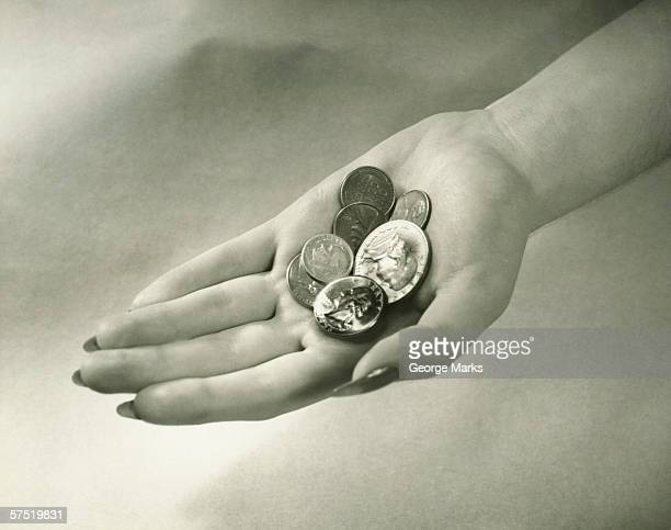 Woman holding American coins, close-up of hand, (B&W)
