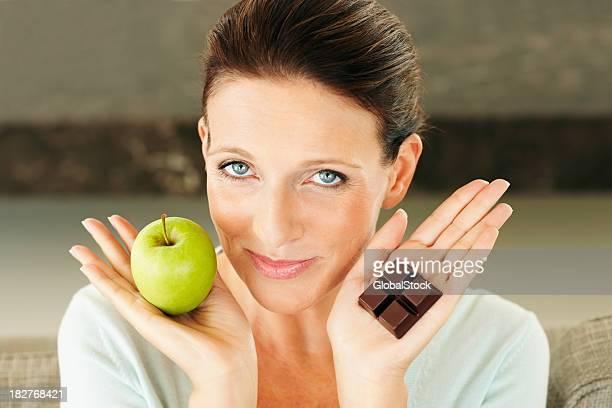 Frau hält einen Apfel und ein Stück Schokolade