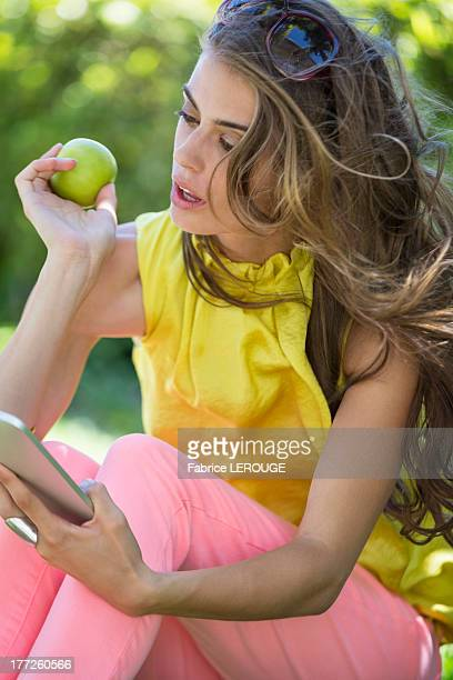 Woman holding an apple and looking at a digital tablet