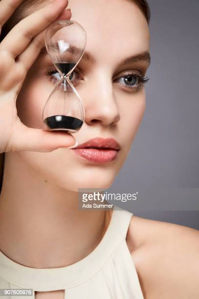 woman holding  an hour glass in front of her eye