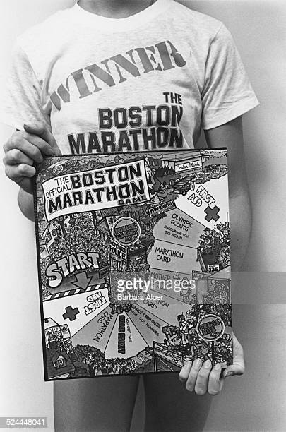 A woman holding an illustration for the Boston Marathon board game Boston Massachusetts USA February 1979