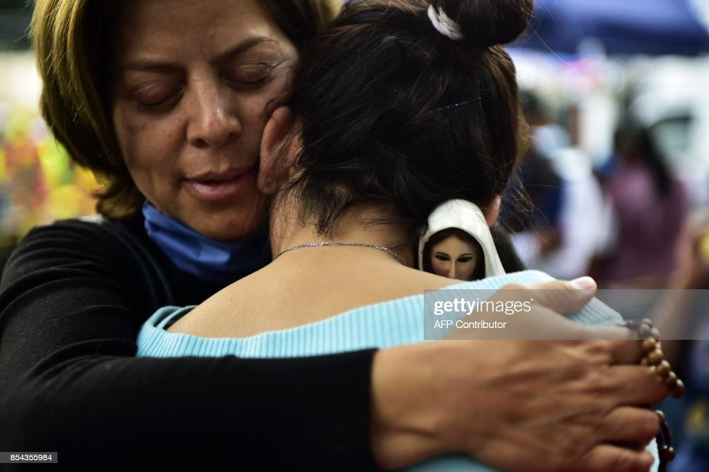 TOPSHOT - A woman (black jersey) holding an image of the Virgin of Fatima comforts a relative of people who are presumed still buried under the rubble from a building toppled by the 7.1-magnitude quake that struck central Mexico one week ago and waits for news, in Mexico City on September 26, 2017. A week after an earthquake that killed more than 300 people, a shaken Mexico was torn Tuesday between trying to get back to normal and keeping up an increasingly hopeless search for survivors. /