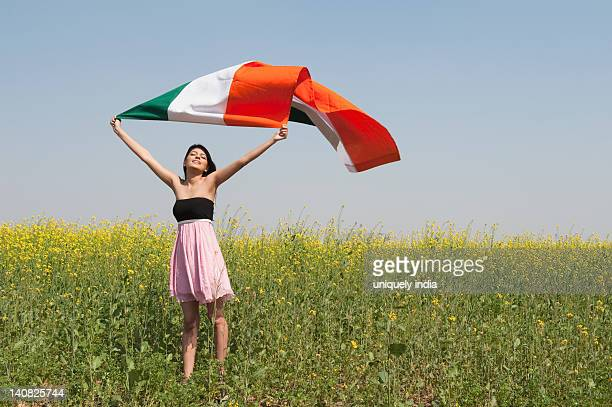 Woman holding an Indian flag in an oilseed rape field