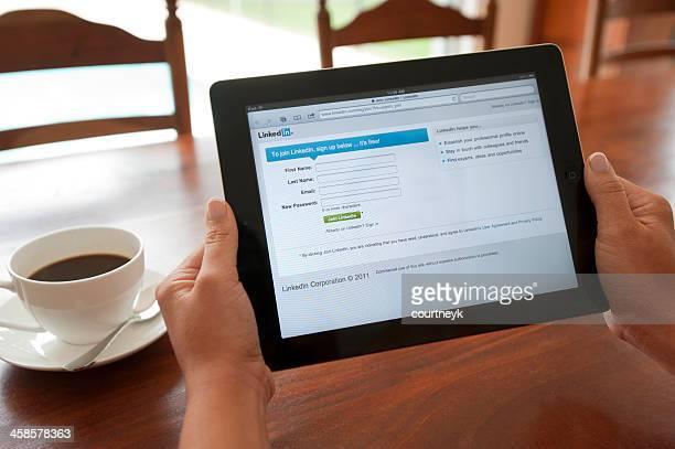 Femme tenant un ipad montrant l'écran de connexion Linkedin