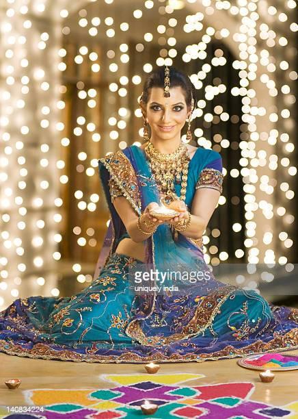 Woman holding an oil lamp near rangoli at Diwali festival