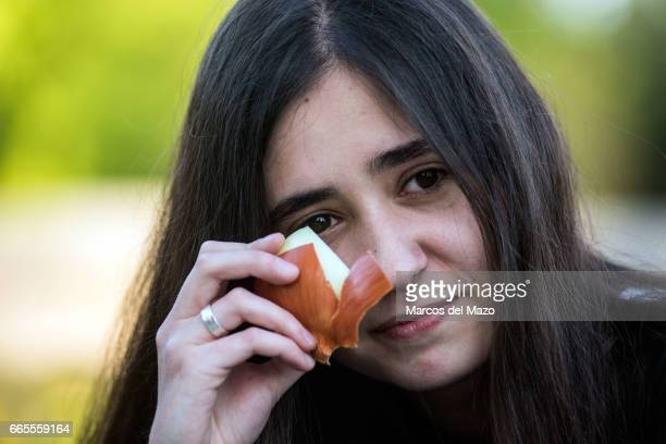 A woman holding an onion near her eyes trying to cry during an event organized through Facebook under the name 'Gathering for crying' celebrated in...