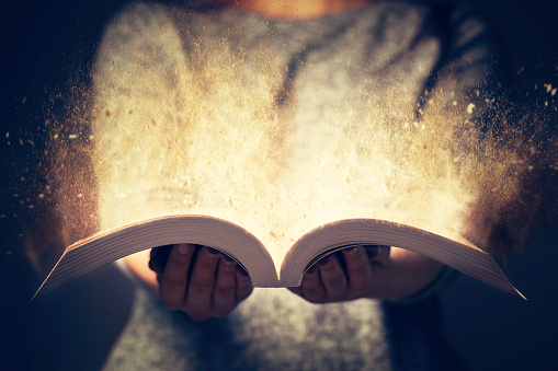 Woman holding an open book bursting with light. 921871490