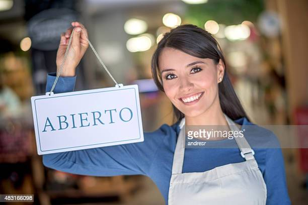 Woman holding an open sign in spanish