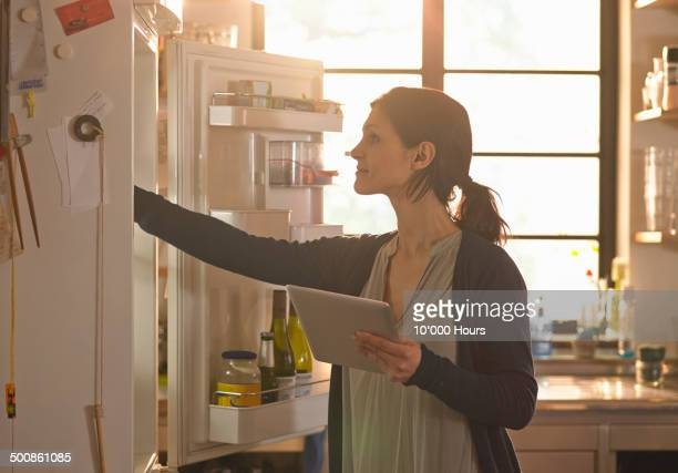 woman holding an tablet computer whilst looking in the fridge - refrigerator stock pictures, royalty-free photos & images
