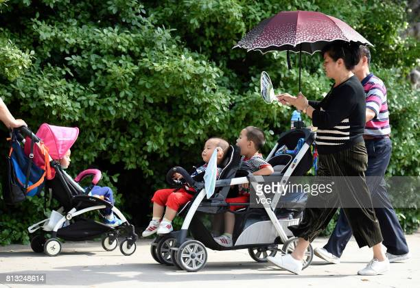A woman holding an umbrella and waves a fan as two kids sit in a tandem stroller on July 12 2017 in Beijing China The dog days of summer start from...