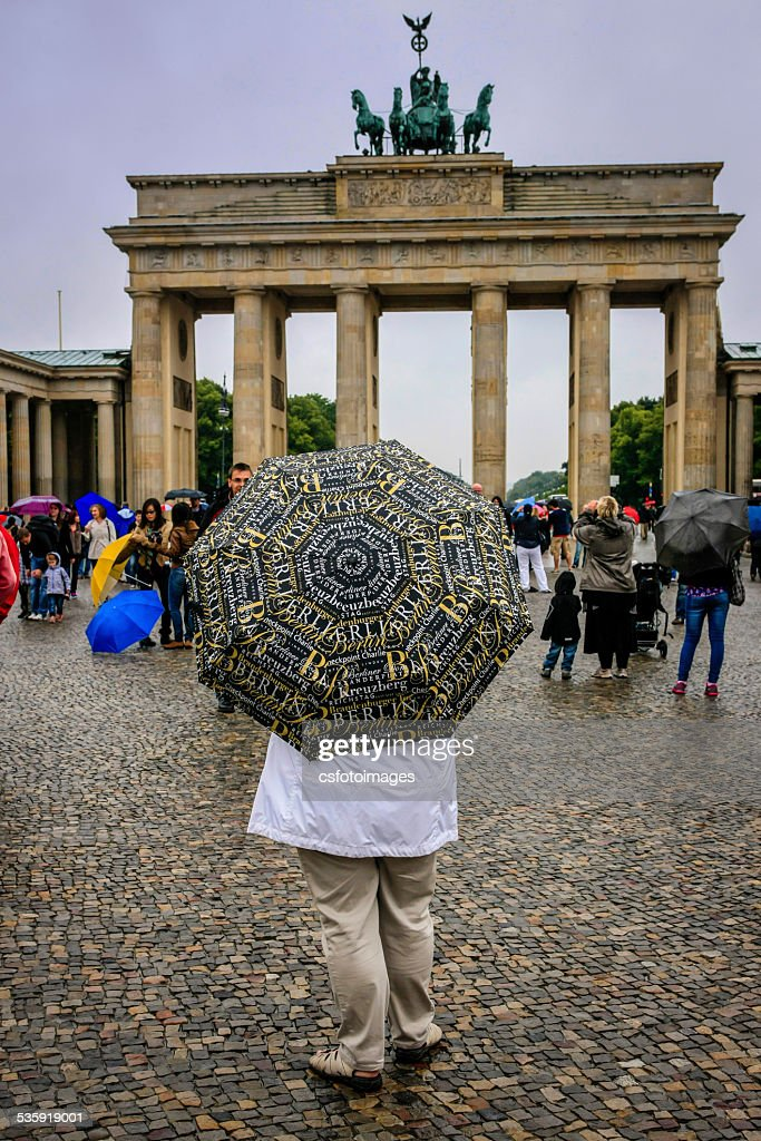 Woman holding an umbrella on a rainy day in Berlin : Stock Photo